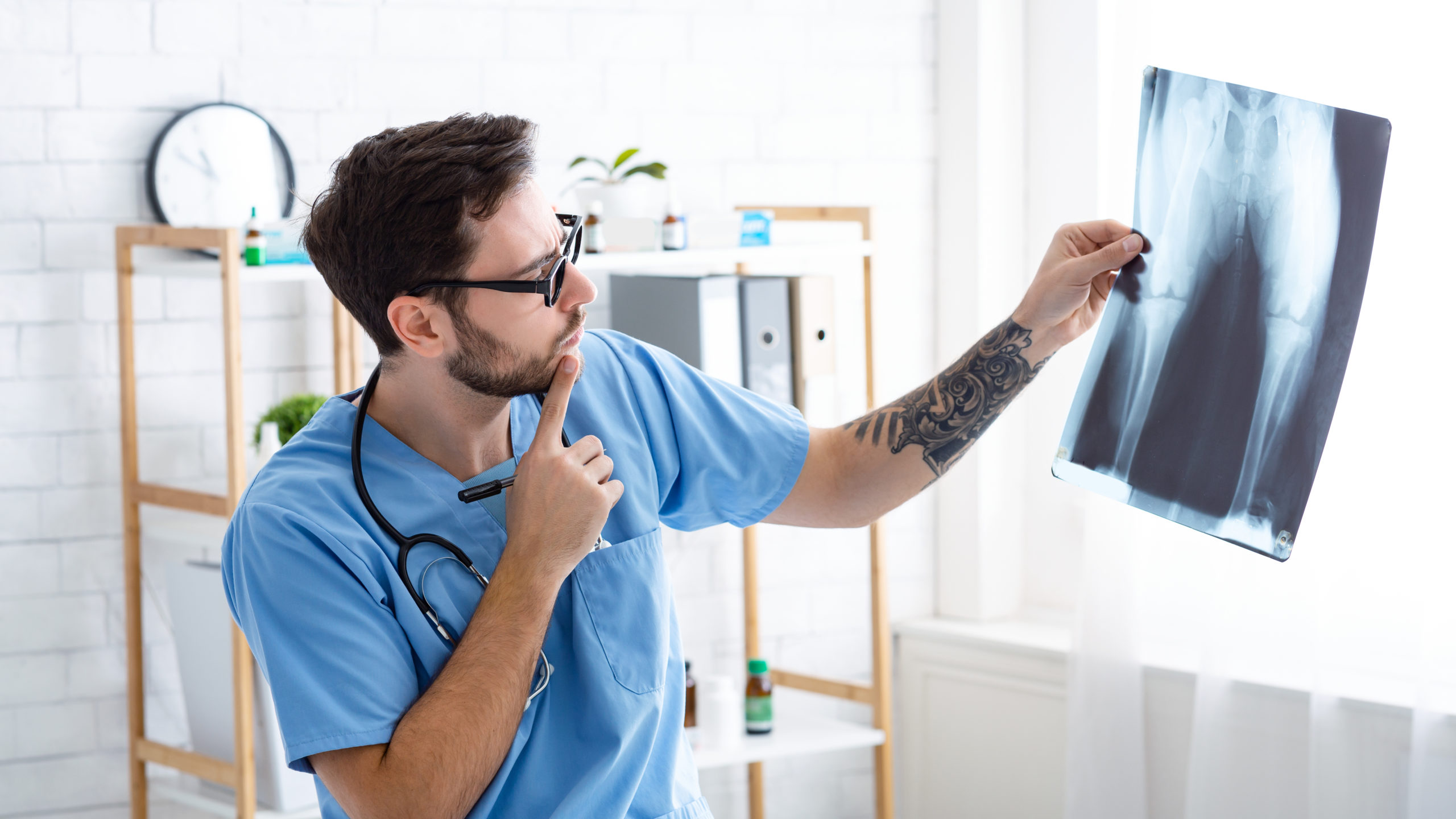 Male veterinary surgeon looking at xray at animal hospital, panorama